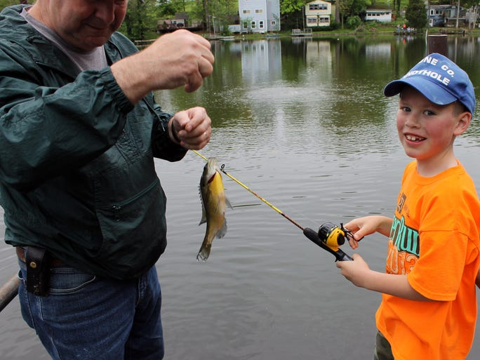 Eight-year-old Ian Halpin of Burlington, right, has just caught a fish at Boone Lake, Walton.  With him is volunteer Chet Hayes from California, Ky.