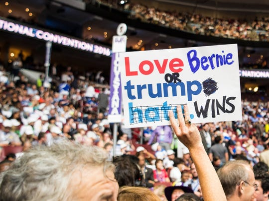A Bernie Sanders supporter carries a sign during the Democratic National Convention at Wells Fargo Arena in Philadelphia on July 25, 2016.