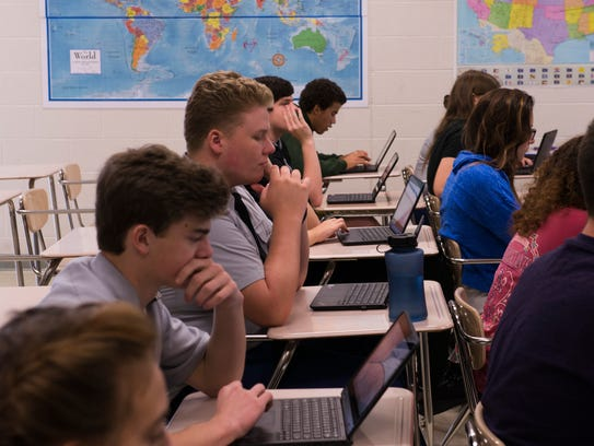 Students take notes and follow along on their laptops