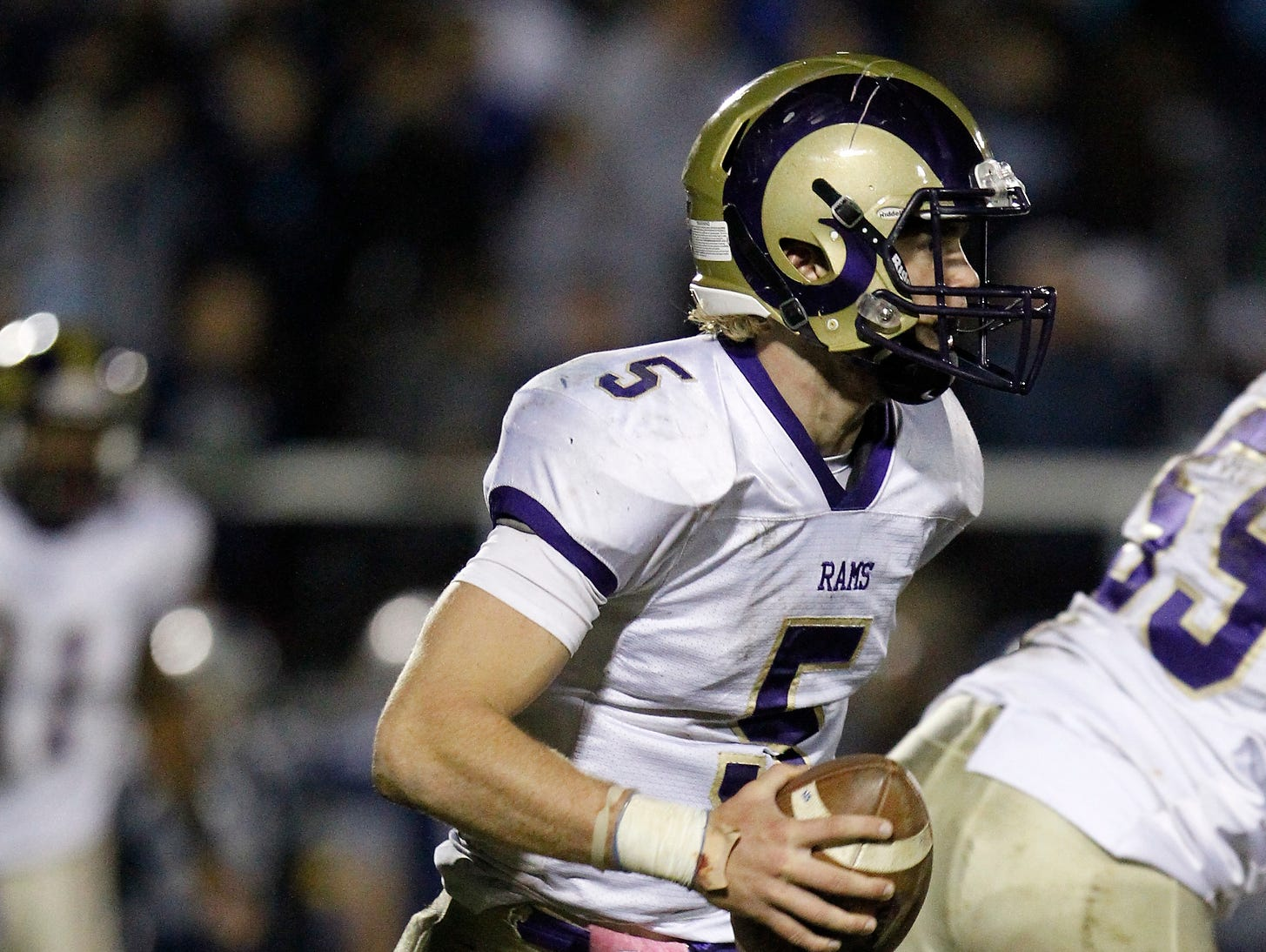 Clarkstown North quarterback Jack Abrams (5) runs out of the pocket during their 21-7 loss to John Jay High School in the class AA semi-final football game in East Fishkill on Friday, Oct. 30, 2015.