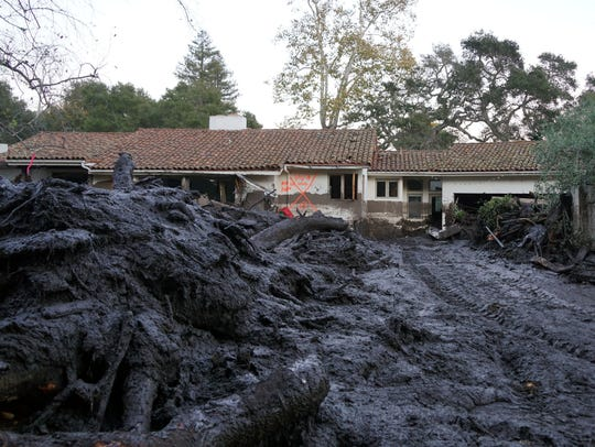 Mud and debris litter the front yard of a home in Montecito