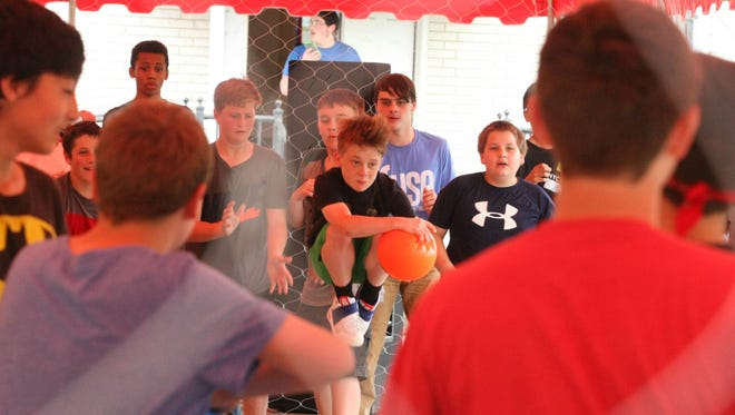 Boy jumps in air before throwing ball at dodgeball game between youth and local police at Erin Church of the Nazarene.