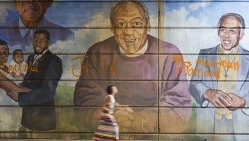 A woman walks past a mural depicting Bill Cosby, center, on July 8, 2015, in Philadelphia.