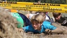 Kids crawl through the mud during the Delta Down & Dirty.