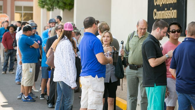 Visitors line-up outside the Arizona Corporation Commission before a meeting to oppose a plan by Arizona Public Service Co. to increase fees on solar customers in Phoenix on Tuesday, August 18, 2015.