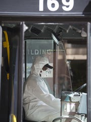 The driver of a New Orleans RTA bus wears protective clothing to protect against the coronavirus.