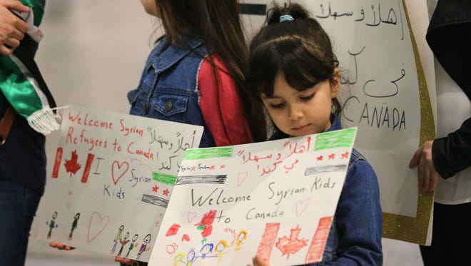 FILE - Maryam and Nore Kasmeih await refugees at the airport in Mississauga, Ont. Their Syrian relatives have fled to Turkey. The Canadian government is restoring healthcare benefits to refugees, including no-cost hospital and medical treatment, examinations and vaccinations, by April 1.