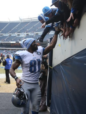 Detroit Lions Calvin Johnson hands off his gloves to fans after the 20-14 win over the Chicago Bears on Sunday, December 21, 2014 at Soldier Field in Chicago.