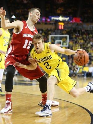 Michigan's Spike Albrecht drives against Wisconsin's Sam Dekker during the first half at Crisler Center.