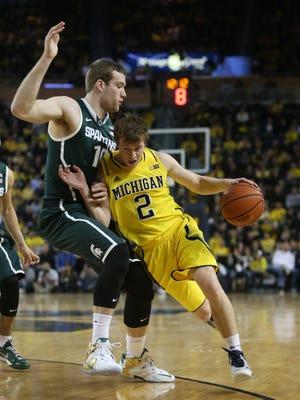 Michigan's Spike Albrecht, right, drives against Michigan State's Matt Costello on Feb. 17, 2015, at the Crisler Center in Ann Arbor.