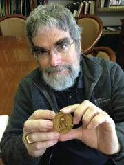 In a Nov. 2014 photo at the Cranbrook Institute of Science, Vatican astronomer and Jesuit Brother Guy Consolmagno, , displays the Carl Sagan Medal he was awarded in 2014 for his distinguished work in explaining the planetary sciences to the public.