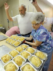 Bruce Lightner gets out of the way of Joann Rohrbaugh  as she places a tray of no-suger added apple dumpling on the counter in the kitchen of the Windy Hill Senior Center in Spring Grove on Friday, Nov. 6, 2015. The duo were participating in the annual apple dumpling fund raiser, which yields about 1300 dumplings over two days and benefits the center.