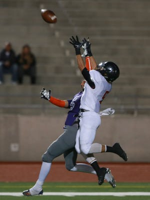 Cooper receiver Jordean Salas, right, and Eastlake defensive back Thomas Martinez leap for a long fourth down pass during the first quarter Friday. Martinez intercepted the pass.