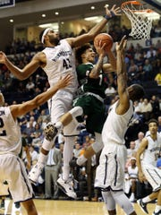 Wagner's Aaren Edmead gets trapped shooting between Monmouth's Chris Brady, left, and Je'lon Hornbeak, right, during the first half, Sunday, December 13, 2015, in West Long Branch.