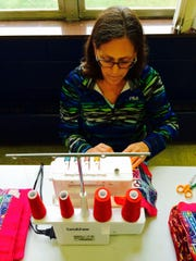 Carol Pedersen Teevens sews to make reusable, washable