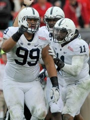 Penn State's Austin Johnson, left, celebrates a sack with teammate Brandon Bell (11) during Saturday's 24-17 loss to Georgia in the TaxSlayer Bowl in Jacksonville, Fla. After the game, Johnson announced he will enter the NFL Draft and skip his final year of eligibility.