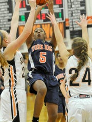 York Suburban's Parker Faircloth-Henise, left, and Olivia Gettle, converge on William Penn's Chyna Steele as she goes up for a shot during the Trojan's 50-38 victory on Monday, Jan. 11, 2016