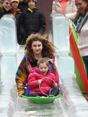 Piper Wetzler, 3, and her cousin Kathryn Scott, 11 ride down an ice slide at Cherry Lance during their visit to FestivIce in York city in 2016.