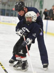 "Rich Garrison, right, gives some help to Kai Gibson-Wright, who was on the ice for his first session as a member of the York Polar Bears hockey team on Monday, March 7, 2016. Garrison, a disabled Army vet, saw a dire need for a sports team for special needs kids in York County. Where else would they play? ""The world will tell them they can't,"" Garrison said. ""The hockey family will tell them they can."""