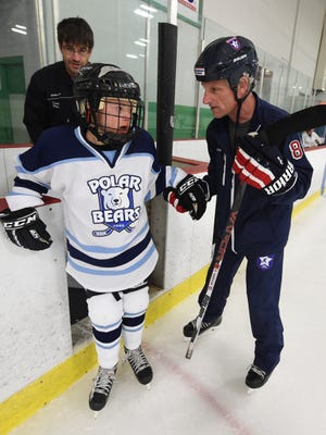 Rich Garrison, right, helps Adam Bernhardt, 12, onto the ice for practice for the York Polar Bears hockey team at the York City Ice Arena on Monday, April 25, 2016. Garrison, of Spring Grove, and a member of the USA Warriors hockey team, established the team for special needs children like Adam, who has Down syndrome.