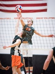A tip-over at the net by Central York's Carter Luckenbaugh (6) is met by Northeastern's Brandon Arentz (23) in Thursday's YAIAA volleyball match at Northeastern High School. The Bobcats won in three games to clinch the league regular-season championship.