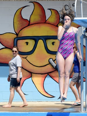Chasity Williams, a seventh-grader from South Western Middle School, grabs a hold of her nose as she jumps off of the diving board and into the pool at Lincolnway Swimming Pool and Sports Club.