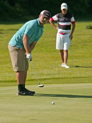 Gavyn Parman watches as Max Lepley putts at hole 8 Monday during a Licking County Junior Golf Association match at Raccoon International.