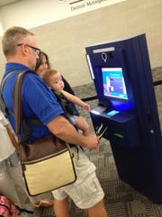 Jack Adams of Florence, Ky. uses an immigration/customs kiosk at Detroit Metro Airport as he arrives on an international flight; his daughter Khloe in his arms.