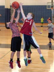 Drew Klaus, 10, a fifth-grader, right, reaches for a rebound Monday morning during Granville's youth boys basketball camp.