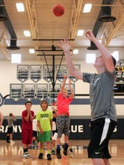 Sullivan Schell, 10, center, takes a shot Monday morning during a competitive game of knockout during Granville's youth boys basketball camp.