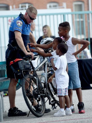 York City Police officer Dan Craven is questioned about what he is wearing while on the playground of Lincoln Charter School during National Night Out. Craven and Lt. Erik Kleynen are part of the city's Neighborhood Enforcement Unit and ride around by bike to patrol the streets.