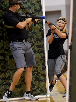 Dallastown Area High School teachers Troy Smeltzer, left, and Laura Workinger battle during a game of laser tag during the school's annual Wellness Fair. The event included various mental health workshops on topics such as suicide prevention, LGBT issues in education and social media's impact on suicide.