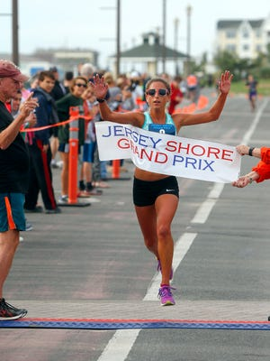 Amanda Marino, Bradley Beach, hits the finish line to win the womens division in the Pier House 5K on the Long Branch promenade Monday morning, September 5, 2016.