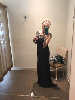 Ellen Creager in a dressing room pondering over a mother-of-the-bride dress.