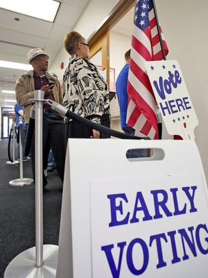 Momoh-Jimoh and Elizabeth Ikharo, of Reynoldsburg, wait in a line Thursday at the Licking County Board of Elections to cast absentee ballots.