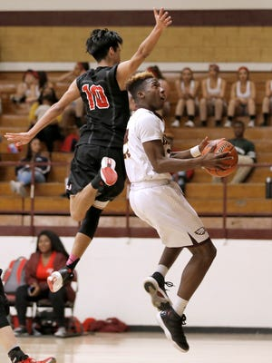 Andress guard Keshon White goes under Jefferson's Miguel Flores for a reverse Tuesday night at Andress High School.
