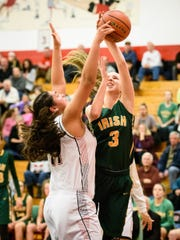 Dover's Gabrielle Coley (11) blocks the shot of York Catholic's Abby Pilkey (3) in a YAIAA girls basketball game at Dover Area High School on Wednesday, Dec. 21, 2016. Dover won 72-62.