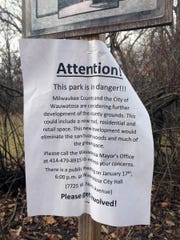 A flier taped to a sign outside an isolated woods at the site of the old Milwaukee County insane asylum carries misinformation that the City of Wauwatosa intends to eliminate the woods as part of proposed development at the County Grounds. Mayor Kathy Ehley has pledged to protect the isolated woods from development.