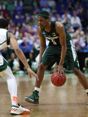 Michigan State guard Cassius Winston dribbles during
