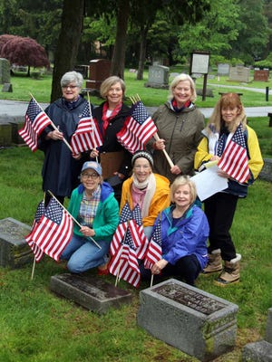 The Piety Hill Chapter of the Daughters of the American Revolution, shown here placing American flags on graves at Birmingham's Greenwood Cemetery, will co-host (along with the City of Birmingham) the city's Veterans Day ceremony Nov. 11.