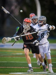 Dallastown's Nate Downey, right, knocks the ball away from Central York's Alex Kilgour, center, during a game last season.