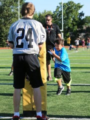 Plymouth player Seth Thompson holds up the blocking bag for Sunshine's camper Max Dean. In the background is Pat O'Connell, assistant coach for the Wildcats. .