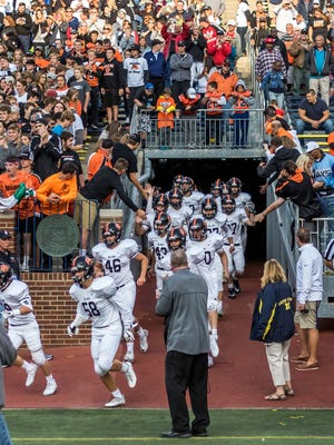 Brighton football players come out of the tunnel at Michigan Stadium before their season opener against Belleville on Aug. 24, 2017.