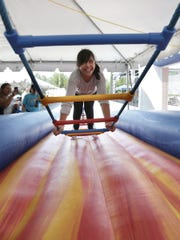 Abby Mendoza attempts to cross the rope ladder at St. Anthony Seminary's annual bazaar.