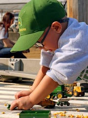 Laramie Massie, 2, of Coshocton, played with farm machinery