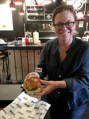 Traci Des Jardins holding an Impossible Burger at B Spot burgers in Royal Oak on Sept. 15, 2017.