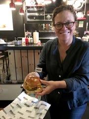 Traci Des Jardins holding an Impossible Burger at B