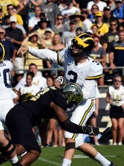 Michigan's Wilton Speight is pressured Purdue's Gelen