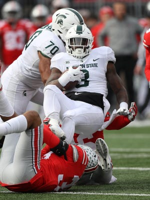 Michigan State's LJ Scott is tackled by Ohio State's Chris Worley in the third quarter Saturday, Nov. 11, 2017 at Ohio Stadium in Columbus, Ohio.