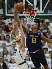 Michigan State forwards Gavin Schilling and Ben Carter rebound against Notre Dame forward Elijah Burns in the first half Thursday.